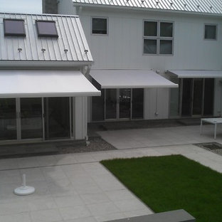 Photo of a medium sized contemporary back patio in New York with natural stone paving and an awning.