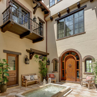 Inspiration for a large mediterranean courtyard tile patio fountain remodel in Orlando with no cover