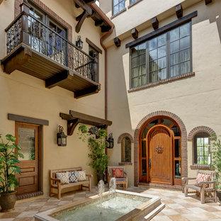 Ispirazione per un grande patio o portico mediterraneo in cortile con fontane, piastrelle e nessuna copertura