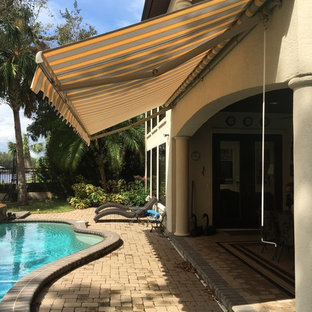 Inspiration for a medium sized mediterranean back patio in Orlando with brick paving and an awning.