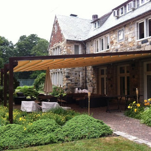 This is an example of an expansive classic back patio in New York with brick paving and an awning.