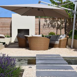Mittelgroßer Moderner Patio hinter dem Haus mit Wasserspiel und Kies in Sonstige