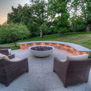 Idee per un grande patio o portico tradizionale dietro casa con un focolare, cemento stampato e un tetto a sbalzo