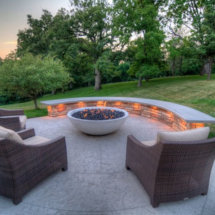 Large transitional backyard stamped concrete patio photo in Cedar Rapids with a fire pit and a roof extension