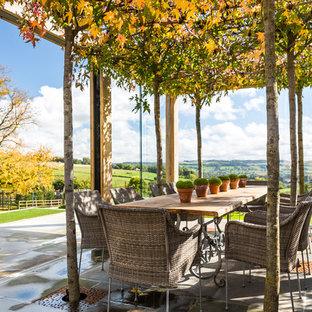 Idee per un grande patio o portico country con una pergola e pavimentazioni in pietra naturale