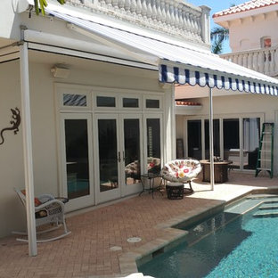 Large world-inspired back patio in Tampa with brick paving and an awning.