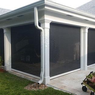 Esempio di un patio o portico tropicale di medie dimensioni e dietro casa con piastrelle e un tetto a sbalzo