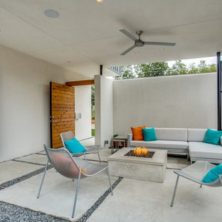 Example of a mid-sized trendy courtyard concrete patio design in Dallas with a fire pit and a roof extension