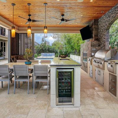 Huge trendy backyard tile patio kitchen photo in Houston with a gazebo