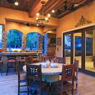 Cette image montre une grande terrasse avec une cuisine extérieure arrière sud-ouest américain avec du carrelage et une extension de toiture.