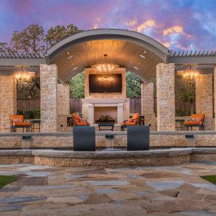 Ispirazione per un grande patio o portico dietro casa con un caminetto, pavimentazioni in pietra naturale e un gazebo o capanno
