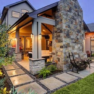 Ispirazione per un patio o portico design di medie dimensioni e dietro casa con pavimentazioni in pietra naturale e un tetto a sbalzo