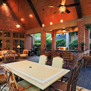 Immagine di un patio o portico stile americano dietro casa con cemento stampato e un tetto a sbalzo