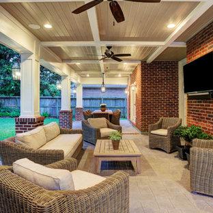 Immagine di un patio o portico chic di medie dimensioni e dietro casa con cemento stampato e un tetto a sbalzo