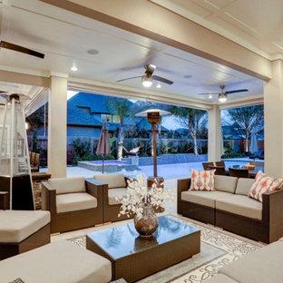 Foto di un grande patio o portico minimalista dietro casa con pavimentazioni in pietra naturale e un tetto a sbalzo