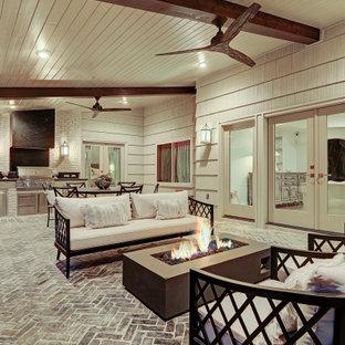 Immagine di un patio o portico chic di medie dimensioni e dietro casa con pavimentazioni in mattoni e un tetto a sbalzo