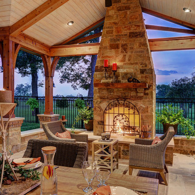 Patio - huge rustic backyard tile patio idea in Houston with a roof extension and a fireplace
