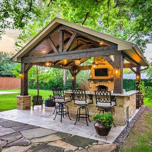 Example of a mid-sized mountain style backyard tile patio kitchen design in Houston with a gazebo