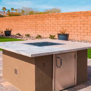 Photo of a large contemporary back patio in Las Vegas with an outdoor kitchen, brick paving and an awning.