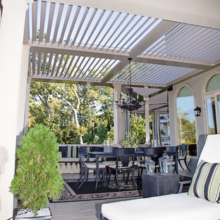 Design ideas for a world-inspired back patio in Los Angeles with tiled flooring and an awning.