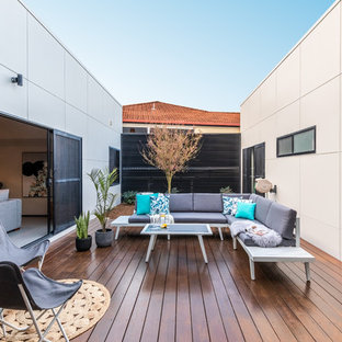 This is an example of a modern courtyard patio in Other with decking and no cover.