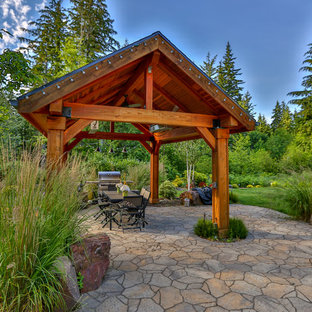 Inspiration for a large craftsman backyard stone patio remodel in Seattle with a gazebo