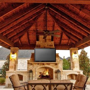Immagine di un grande patio o portico stile rurale dietro casa con un focolare, pavimentazioni in cemento e un gazebo o capanno