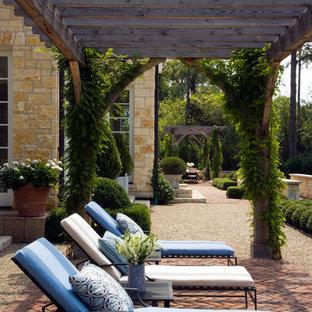 Esempio di un ampio patio o portico classico dietro casa con graniglia di granito e una pergola