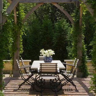 Idee per un ampio patio o portico chic dietro casa con graniglia di granito e un gazebo o capanno