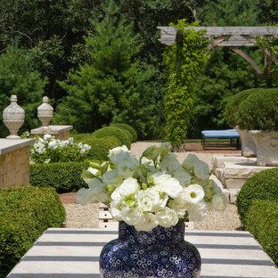 Esempio di un ampio patio o portico tradizionale dietro casa con graniglia di granito e una pergola