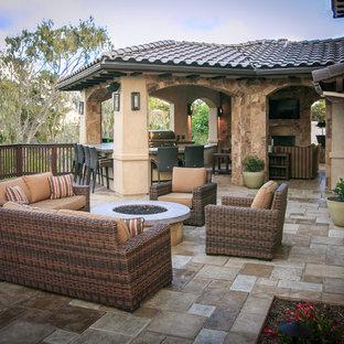 Esempio di un patio o portico mediterraneo di medie dimensioni e dietro casa con pavimentazioni in cemento e un tetto a sbalzo