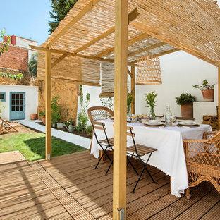 Esempio di un patio o portico mediterraneo di medie dimensioni e dietro casa con un giardino in vaso, pedane e un parasole