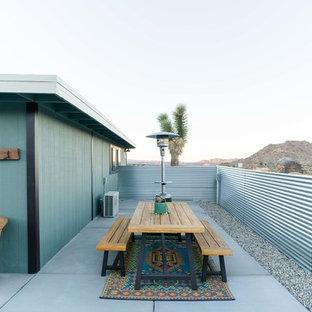 Idee per un grande patio o portico boho chic nel cortile laterale con lastre di cemento e nessuna copertura