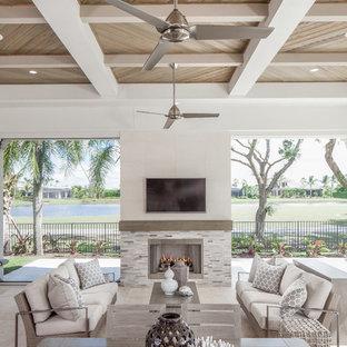 Ispirazione per un patio o portico classico dietro casa con un caminetto e un tetto a sbalzo
