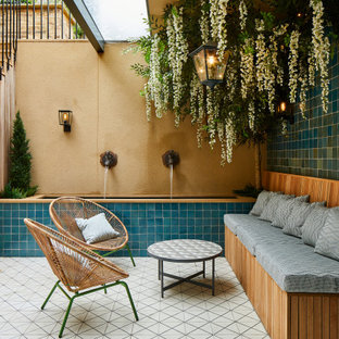 Photo of a mediterranean courtyard patio in London with a water feature and tiled flooring.