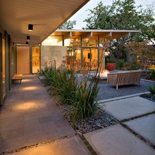 Idee per un patio o portico minimalista in cortile con un focolare, pavimentazioni in cemento e un tetto a sbalzo