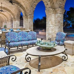 Idee per un ampio patio o portico mediterraneo dietro casa con un tetto a sbalzo