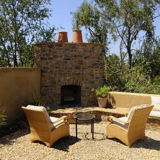 Ispirazione per un grande patio o portico mediterraneo dietro casa con ghiaia, un focolare e nessuna copertura