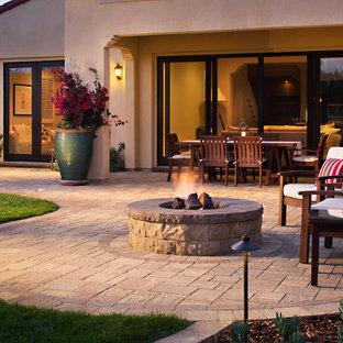 Foto di un patio o portico mediterraneo di medie dimensioni e dietro casa con un focolare, pavimentazioni in cemento e nessuna copertura