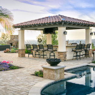 This is an example of a mediterranean back patio in San Diego with an outdoor kitchen, natural stone paving and a gazebo.