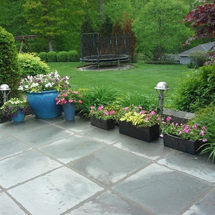 Example of a mid-sized trendy backyard stone patio container garden design in New York with no cover
