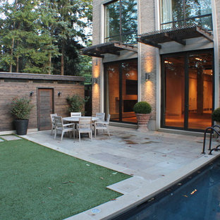 Design ideas for a contemporary patio in Toronto with an awning.