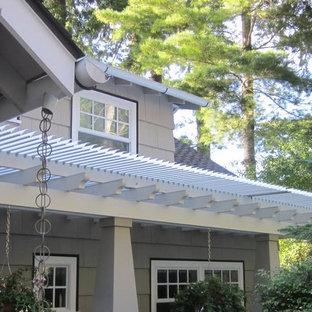 Ispirazione per un patio o portico stile americano di medie dimensioni e dietro casa con pedane e una pergola