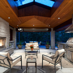 Trendy patio photo in Vancouver with a fire pit and a roof extension