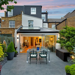 This is an example of a medium sized contemporary back patio in London with a potted garden, natural stone paving and no cover.