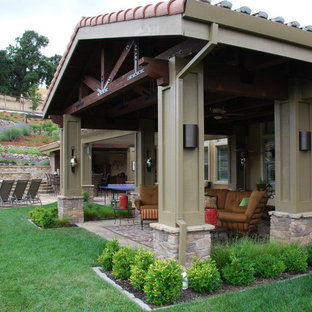 Example of a large tuscan backyard stone patio design in San Francisco with a roof extension