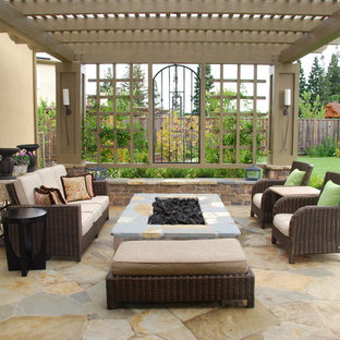 Inspiration for a large mediterranean backyard stone patio remodel in San Francisco with a fire pit and a pergola