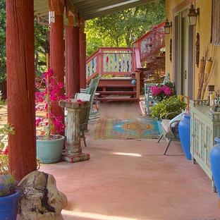 Esempio di un patio o portico etnico di medie dimensioni e dietro casa con fontane, lastre di cemento e un tetto a sbalzo