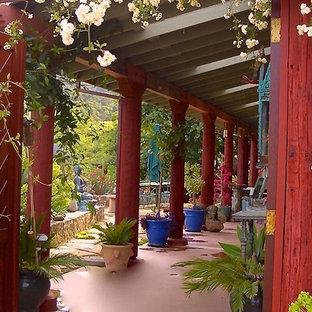 Idee per un patio o portico etnico di medie dimensioni e dietro casa con fontane, lastre di cemento e un tetto a sbalzo
