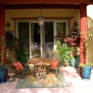 Ispirazione per un patio o portico etnico di medie dimensioni e dietro casa con fontane, lastre di cemento e un tetto a sbalzo